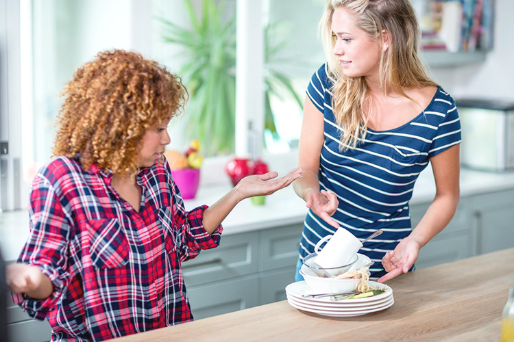 Two girls arguing over dishes